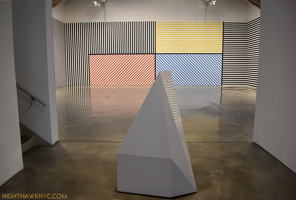 """Complex Form #65,"" 1989, painted wood, 59 x 38 x 40 inches, in front of ""Wall Drawing #368"" @ Paula Cooper."